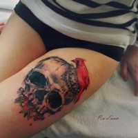 Simple colored thigh tattoo of human skull with red bird