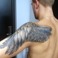 Simple designed big black and white feather wing tattoo on shoulder