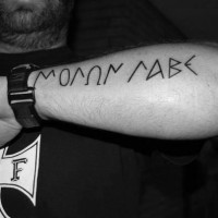 Simple homemade like black ink Latin lettering tattoo on arm