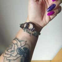 Simple homemade like black ink wrist tattoo of
