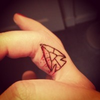 Simple homemade like colored antic bloody arrow head tattoo on finger