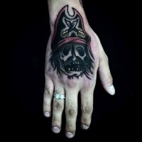 Simple homemade like colored pirate skull tattoo on hand