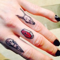 Simple homemade like colored tiny animal skulls tattoo on fingers with coffin