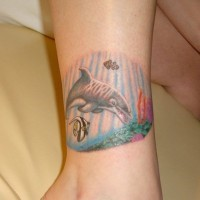 Simple tiny colored dolphin tattoo on ankle