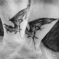 Small black ink ankle tattoo by Inez Janiak of bat