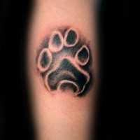Small black ink arm tattoo of animal paw print