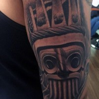 Small black ink detailed tribal statue tattoo on shoulder