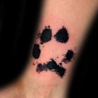 Small black ink wrist tattoo of animal paw