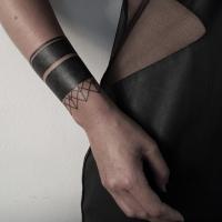 Small black ink wrist tattoo of simple ornament