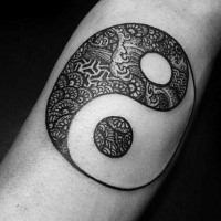 Small black ink Yin Yang symbol tattoo stylized with ornamental flowers