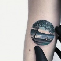 Small circle shaped arm tattoo of big island with tree