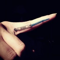 Small detailed blue colored light saber tattoo on point finger