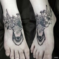 Small engraving style black ink deer tattoo on foot stylized with flowers
