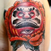 Small illustrative style shoulder tattoo of daruma doll with rose and creepy eye