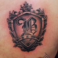 Small shield shaped chest tattoo of old symbol with lettering