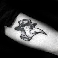 Small simple looking arm tattoo of plague doctors head