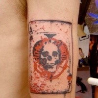 Small watercolor style arm tattoo of card stylized with skull