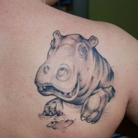 Smiling gray-ink hippo head tattoo on upper back