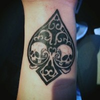 Spades symbol designed with skulls and ornaments black and white tattoo on wrist