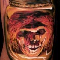 Spooky demon head in a glass jar tattoo