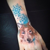 Stippling style colored wrist tattoo of wolf with snowflake