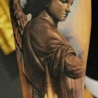 Stonework style colored forearm tattoo of angel statue in old cathedral