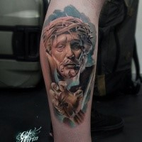 Stonework style colored leg tattoo of Jesus statue with vine