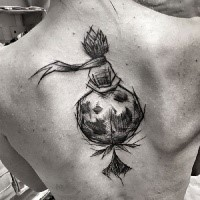 Strange looking black ink upper back tattoo of interesting plant with ribbon