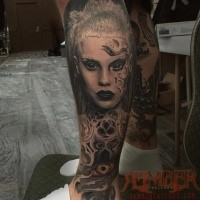 Stunning black ink leg tattoo of demonic woman with eye and ornaments