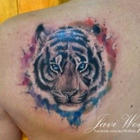 Stunning tiger's head with colorful paint drips shoulder blade tattoo by Javi Wolf with watercolor details