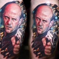 Stunning very detailed colorful Jason Statham movie hero arm tattoo with cool gun