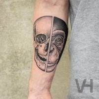 Symmetrical looking black ink forearm tattoo of human and monkey head by Valentin Hirsch