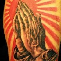 Tatuaggio realistico sul braccio le mani che pregano sul fondo del sole
