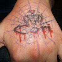 Le tatouage d'inscription avec une couronne embrassant sur la main