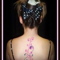 Crossed curls pink tattoo on upper back