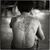 Different notes on upper back circle and flowers tattoo