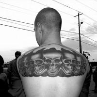 On upper back row of black skulls tattoo