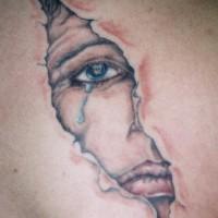 Crying face behind skin rip tattoo