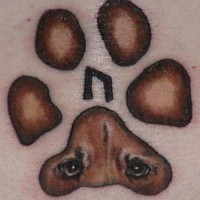 Paw print with dog eyes tattoo