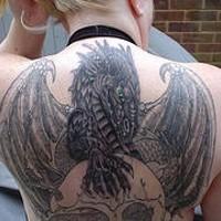 grande drago alato con cragno sulla schiena tatuaggio