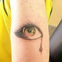 Tatuaje de un ojo verde con lágrimas