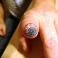 Eyeball on amputated finger chin up tattoo