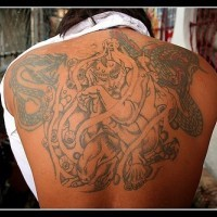 Tatuaje negro de un demonio en espalda