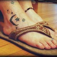 Delicato tatuaggio sul piede polvere di stelle nel cielo e la luna