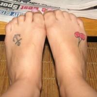 Un petit ancre noir avec le tatouage des cerises sur les pieds