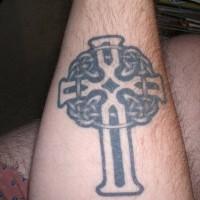 Grande croce nera tatuata sul braccio