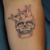 Le tatouage de crâne incolore avec une couronne sur avent-bras