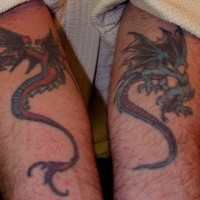 Evil red and blue flying dragons forearm tattoo