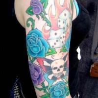 el tatuaje en el brazo de las rosas azules y moradas con cráneo y dados en el fuego