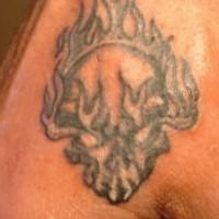 Tatuaggio non colorato sulla mano il teschio nelle fiamme